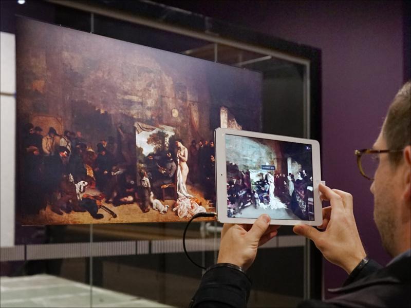 """Visiteur tentant d'utiliser le dispositif de réalité augmentée réalisé par Orange pour informer les visiteurs sur le tableau """"l'Atelier du peintre"""" de Gustave Courbet - Crédit: Flick Creative Commons / Jean-Pierre Dalbéra"""